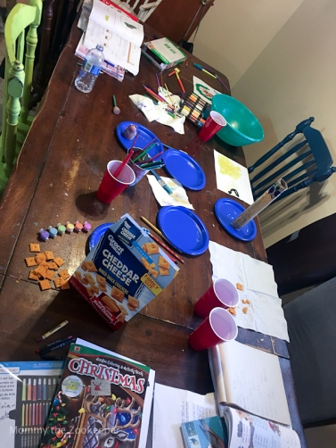 messy table with art supplies and snacks
