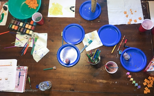 school table from above with paint books and snacks