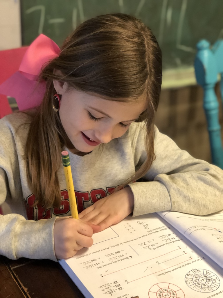 young girl with a pink bow writing in a math workbook