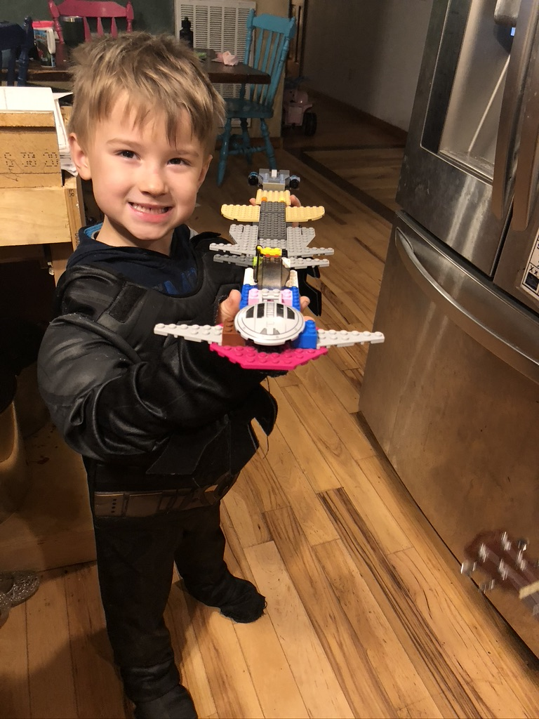 young boy in a costume showing off a lego creation